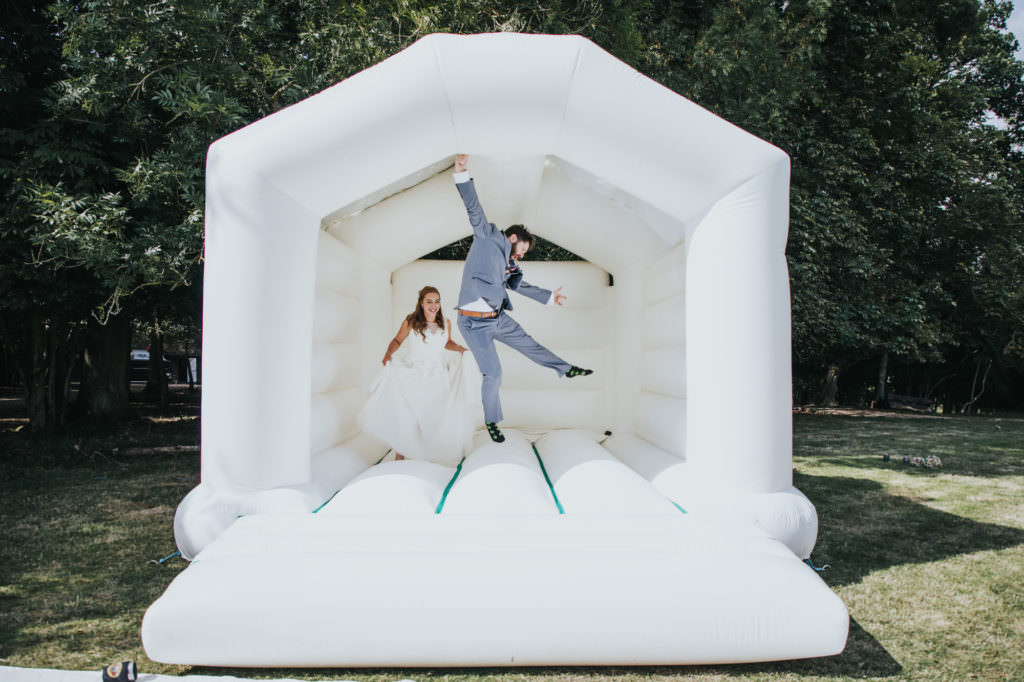 Bride and groom at the bouncy castle - tipi wedding - Sussex Wedding Photography