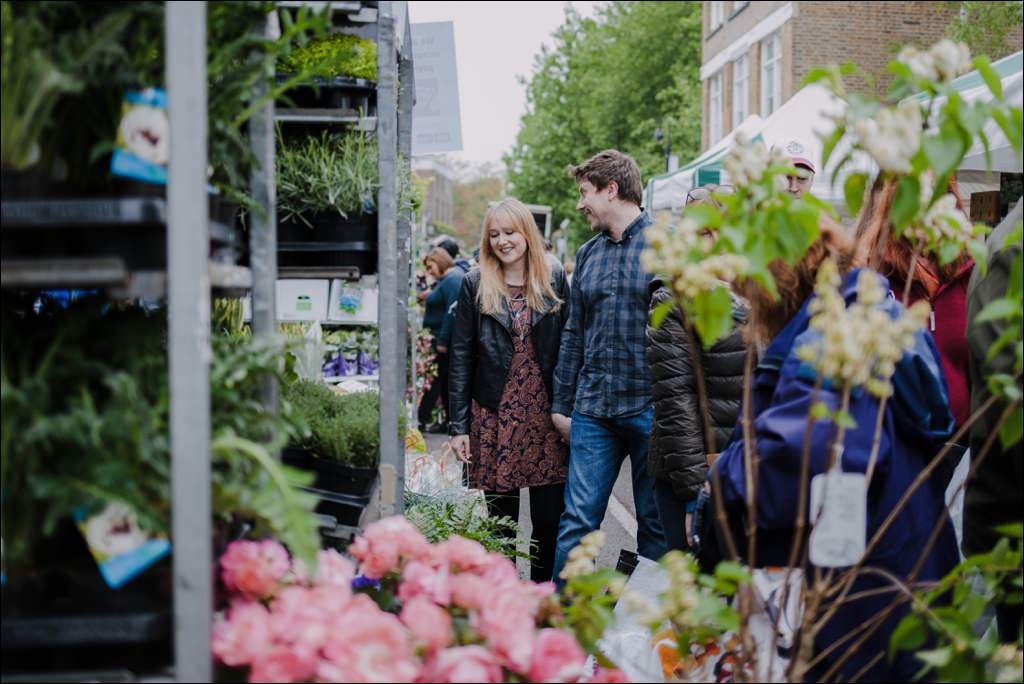 Couple walking down the Columbia Road Flower Market at their Shoreditch engagement shoot