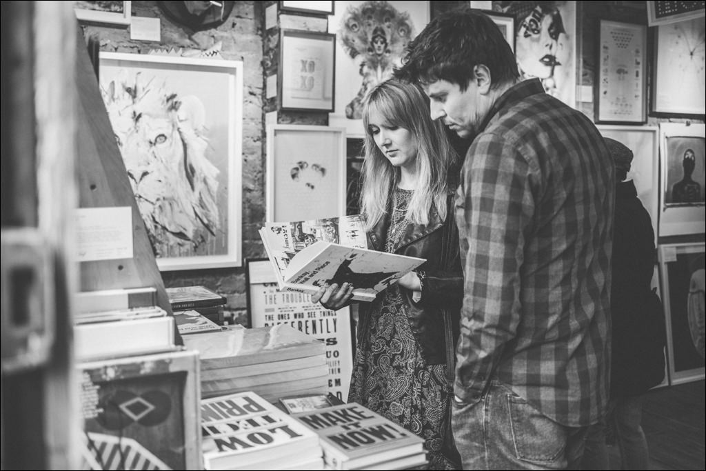 Couple browsing books at the Columbia Road Flower Market at their Shoreditch engagement shoot