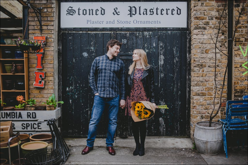 Couple with sunflowers at the Columbia Road Flower Market at their Shoreditch engagement shoot