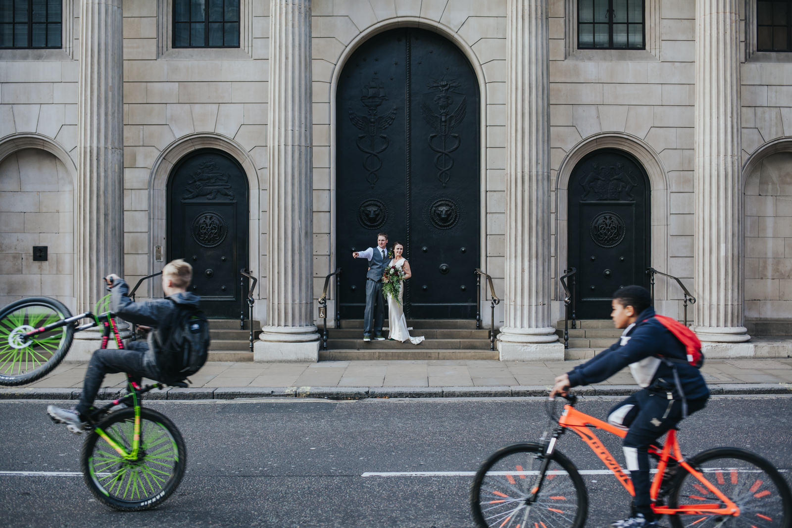 Bride and groom posing in Bank with cyclists photo bombing - Modern London wedding