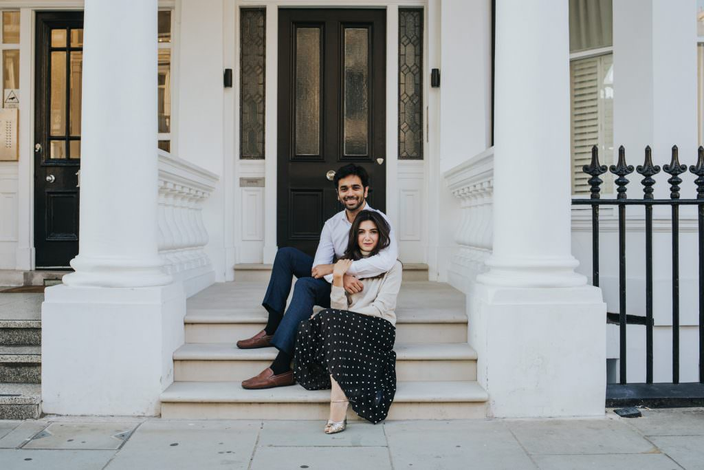 Picture of a couple sitting on the steps of their home in South Kensington