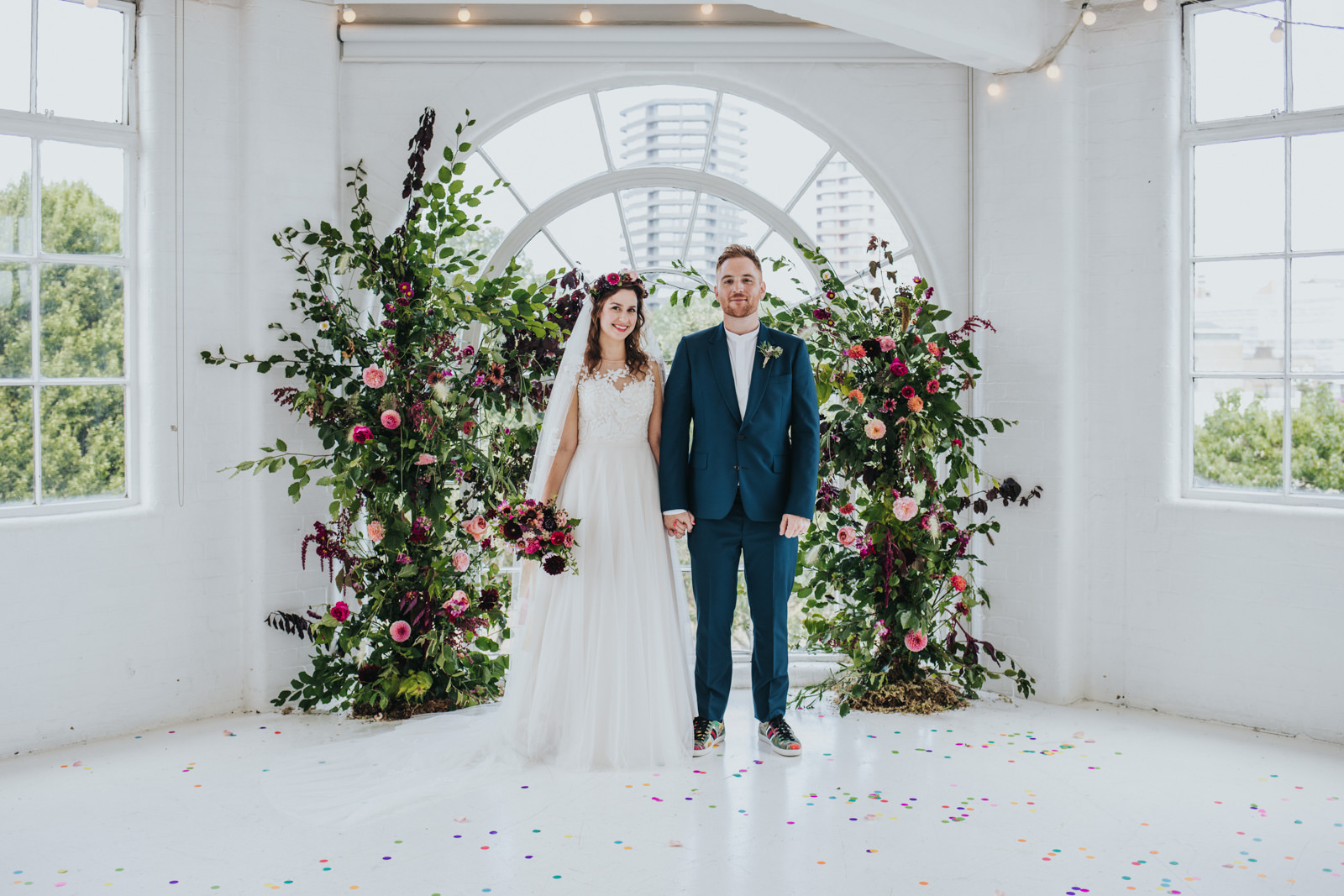Portrait of bride and groom at the Wimbourne House wedding with floral arch