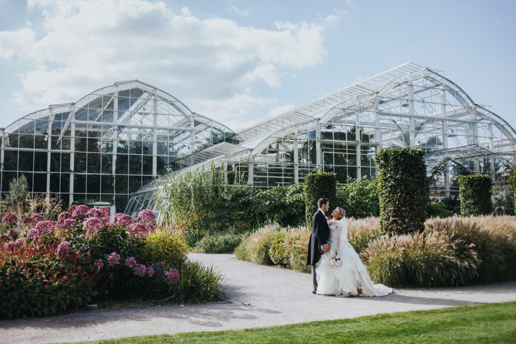 Bride and groom in front of the Glasshouse - Wisley Garden Wedding