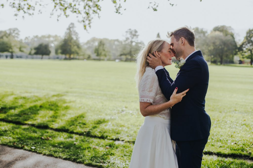 Intimate wedding ceremony in Hackney - groom kissing bride on a forehead in hackney downs park