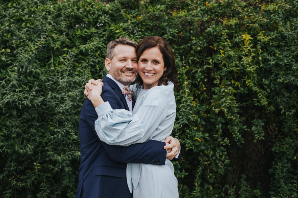 Micro wedding in Hackney - couple hugging in front of greenery