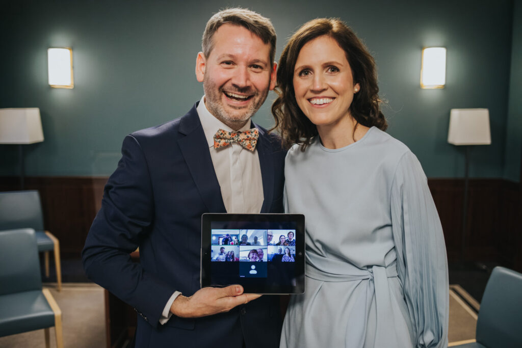 Micro wedding in Hackney - couple with an ipad and family members on zoom